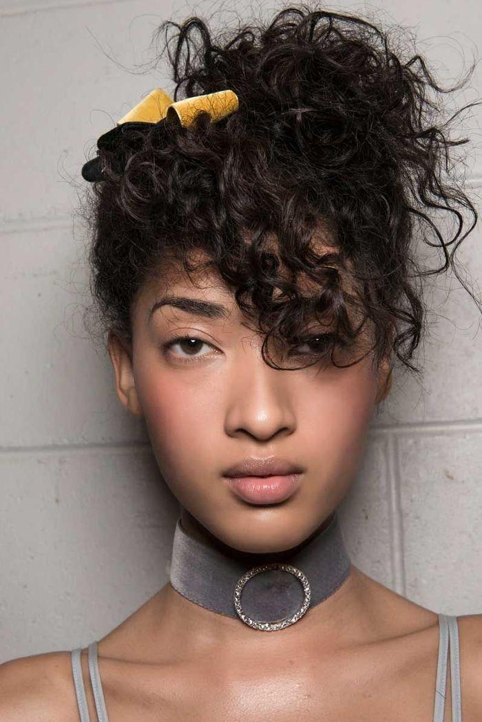 Coiffure facile : cheveux bouclés relevés en chignon flou