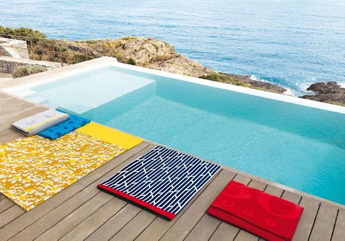 Une terrasse avec piscine colorée grâce aux serviettes de bain