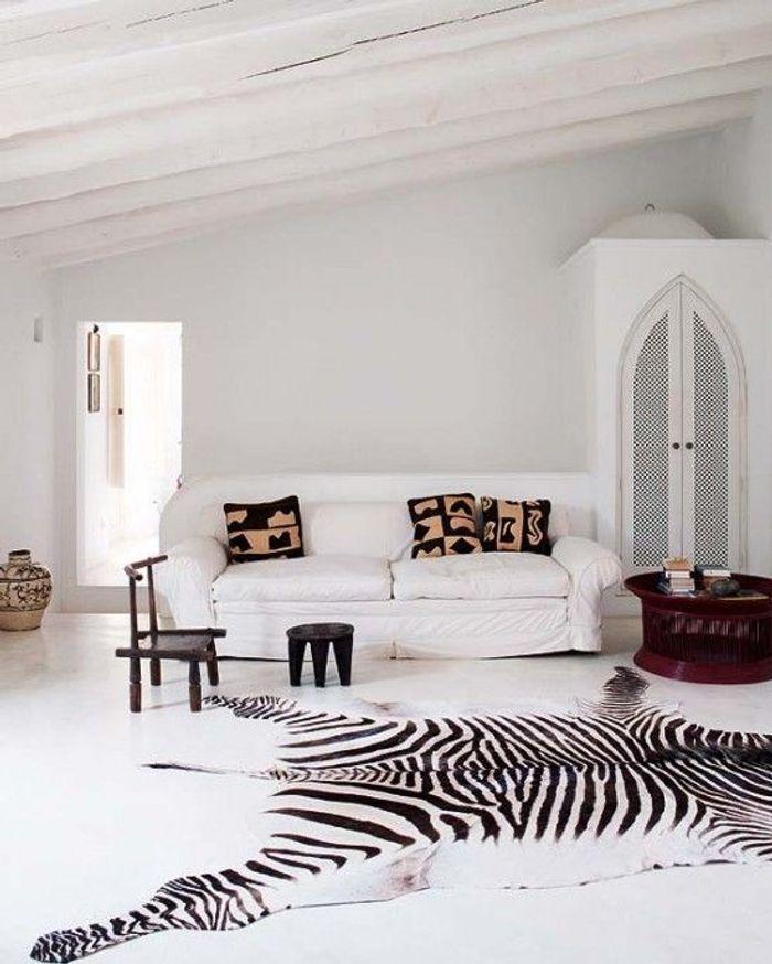 Le mix tapis zèbre, tabouret en bois, poterie et coussins imprimés