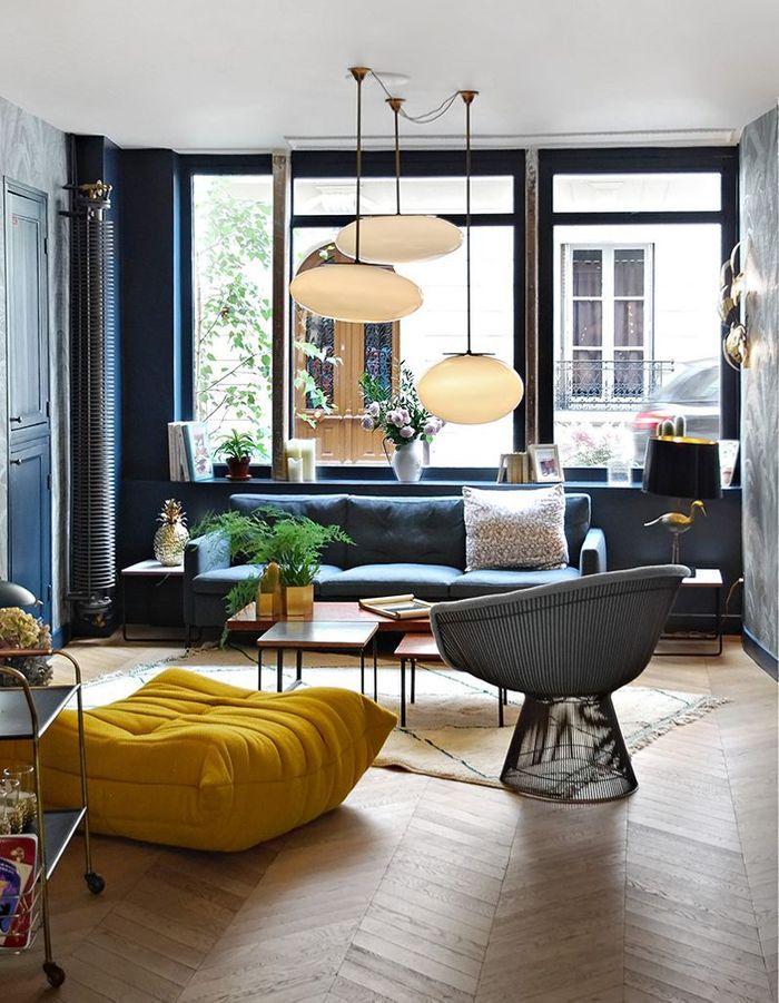 Le pouf Togo jaune safran dans un salon bleu nuit