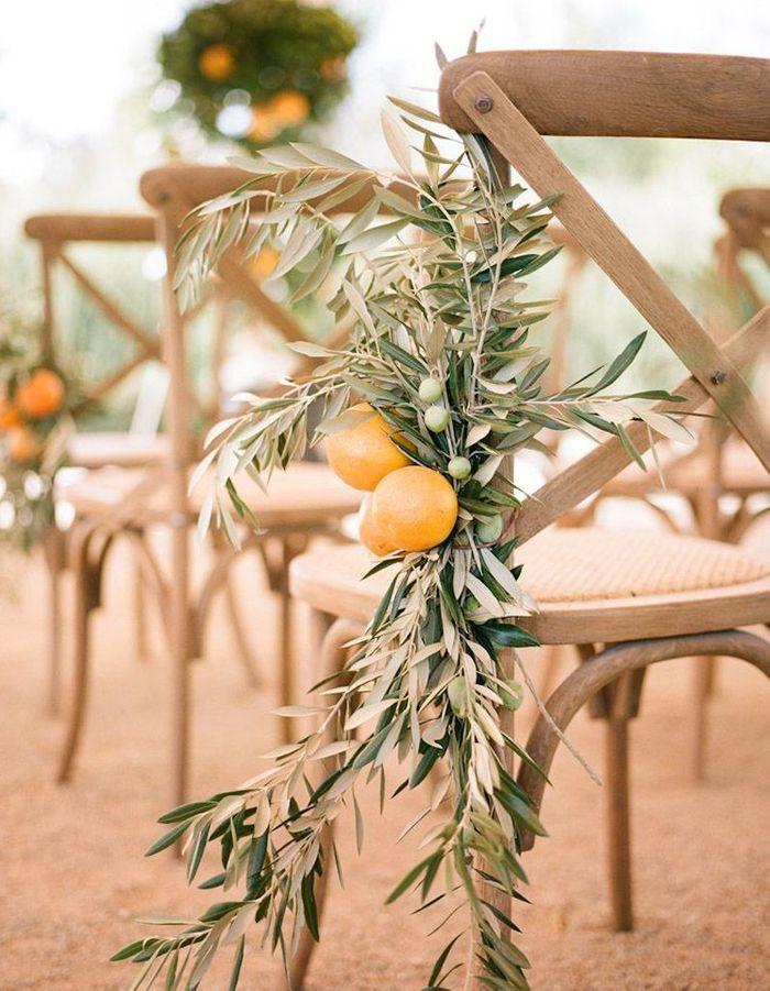 Amener une touche provencale à la cérémonie de mariage via des branches d'olivier et des agrumes fixés à chaque chaise