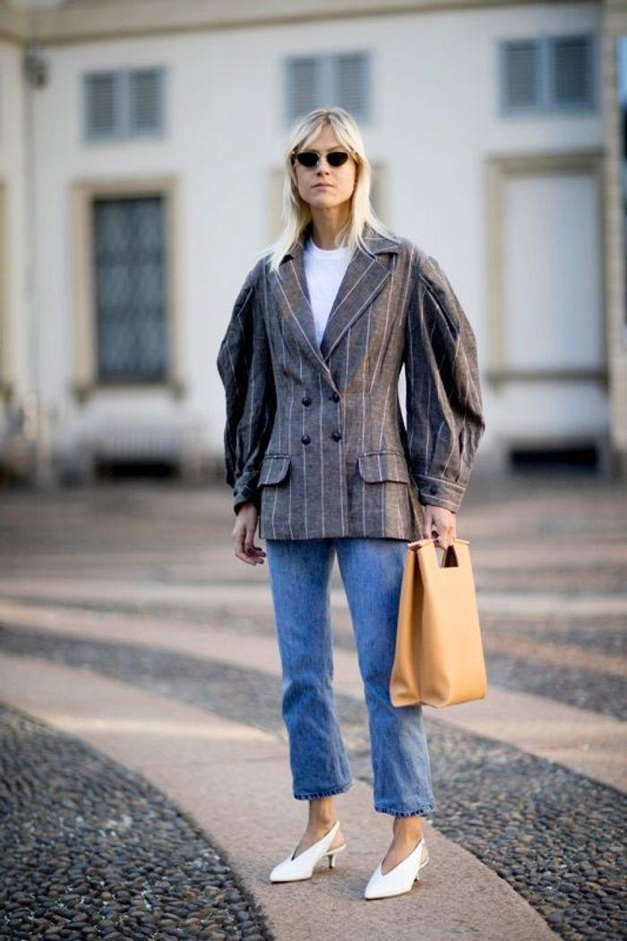 Des escarpins blancs et une veste à manches XXL
